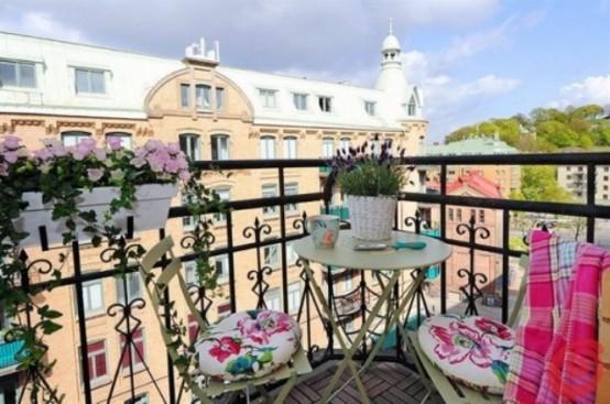 alcuni vasi da ringhiera con fiori, coperte colorate e cuscini floreali sono belli per rinfrescare il tuo balcone per la primavera