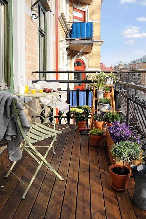 molta vegetazione e fiori luminosi in vasi di legno e terracotta renderanno il tuo balcone un po 'primaverile e un po' rustico