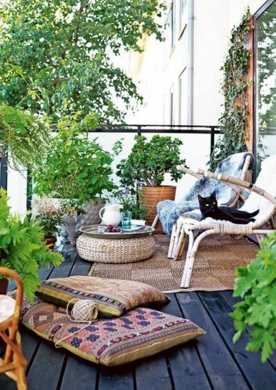 un sacco di verde in cesti, tappeti e cuscini boho, tappeti di iuta e ottomani e una sedia in rattan per un'atmosfera boho