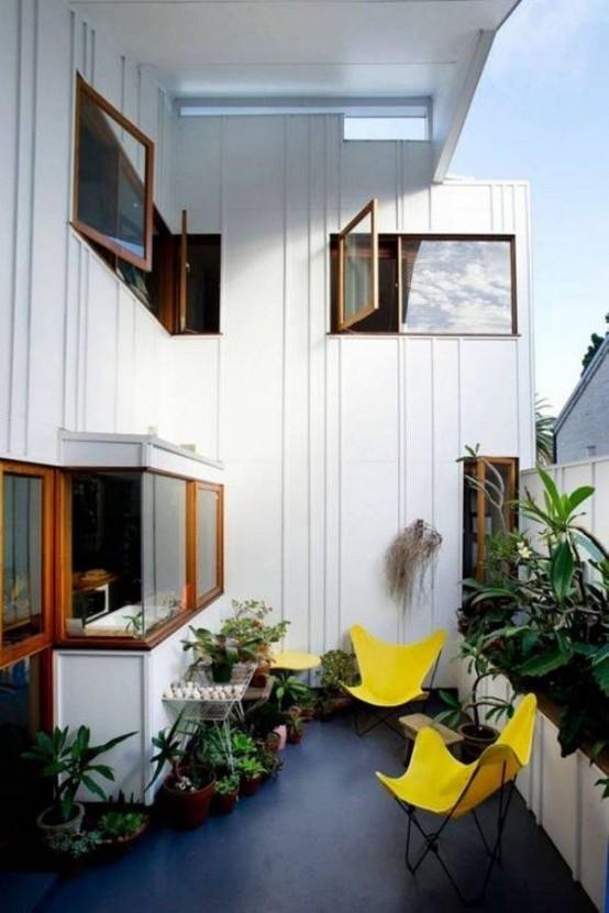 molta vegetazione in vaso e sedie gialle solari renderanno il tuo balcone fresco e invitante