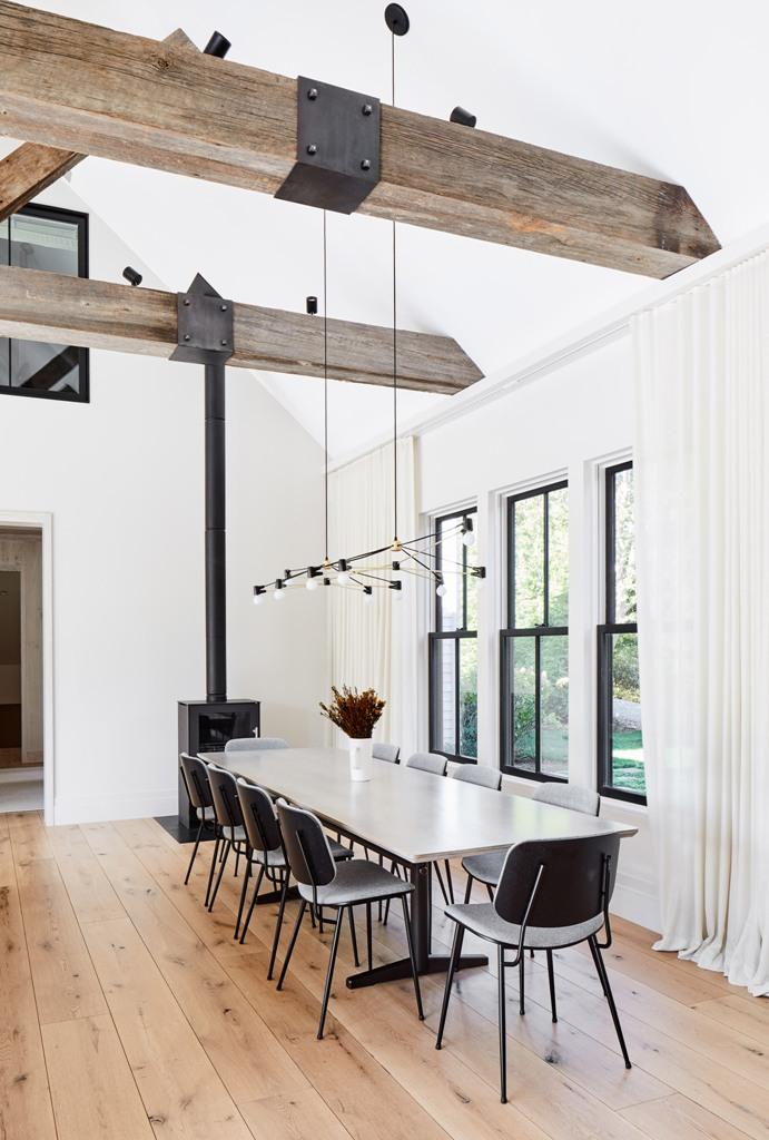 La sala da pranzo è composta da un tavolo bianco, sedie grigie e un focolare
