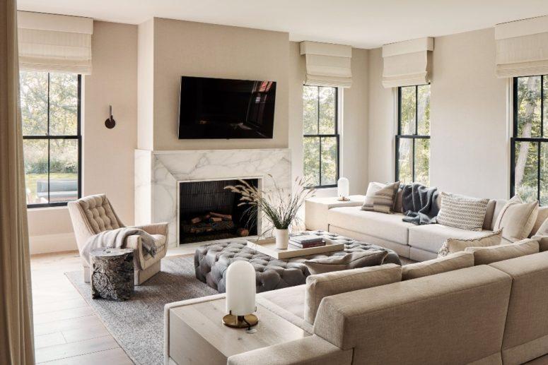 Il soggiorno è arredato con comodi mobili imbottiti, un caminetto rivestito in marmo e molte finestre