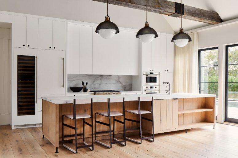 La cucina è realizzata con eleganti mobili bianchi, un alzatina in marmo e un'isola abbinata