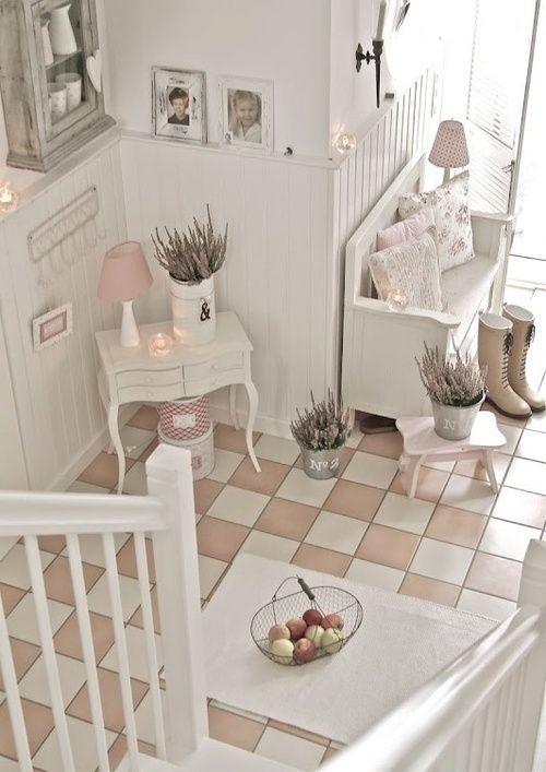 un accogliente ingresso shabby chic neutro con una panca e una piccola console, fiori in vaso, un armadietto in legno grezzo e foto