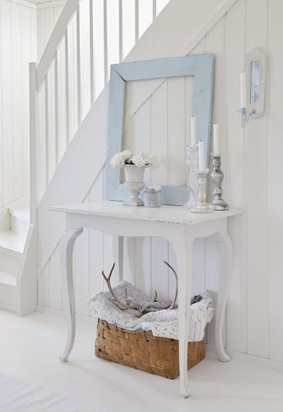 un ingresso shabby chic bianco con un'elegante consolle, una cornice blu, fiori in vaso e un cesto per la conservazione