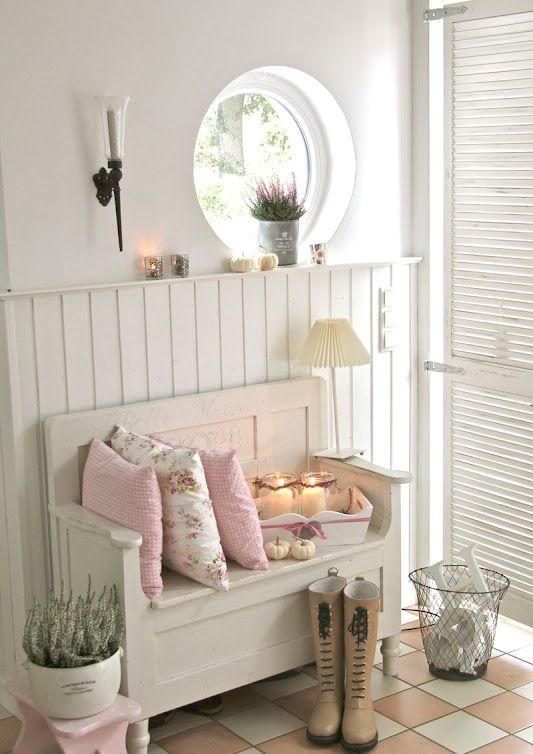 un ingresso shabby chic neutro con battente sul muro, una finestra ad oblò, una panca di legno, vegetazione in vaso e una porta a battente