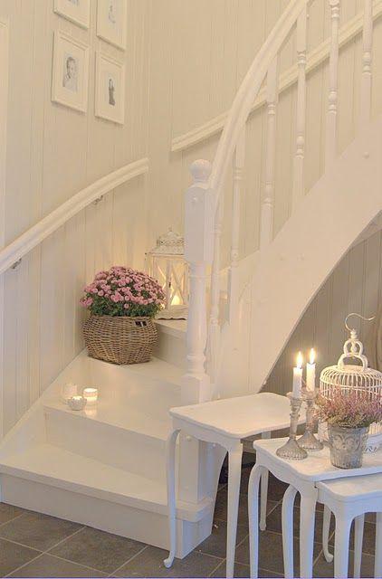 un ingresso shabby chic bianco con tavolini, candele, una gabbia e fiori in vaso