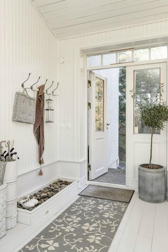 un ingresso neutro con una scatola di ciottoli per scarpe, tappeti, un albero in vaso e un appendiabiti