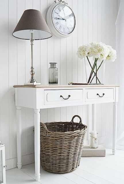 un ingresso shabby chic neutro con una console, una lampada da tavolo, un orologio e un cestino per riporre gli oggetti