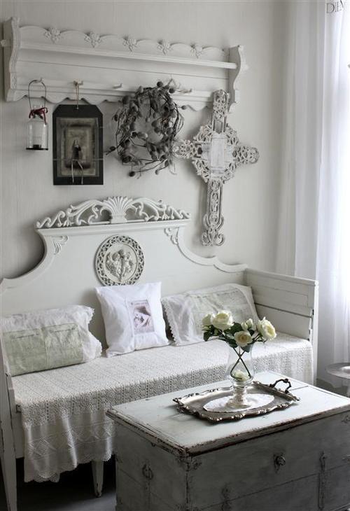 un ingresso bianco, un appendiabiti intagliato, una panca intagliata, un baule per riporre, insegne e lanterne a candela