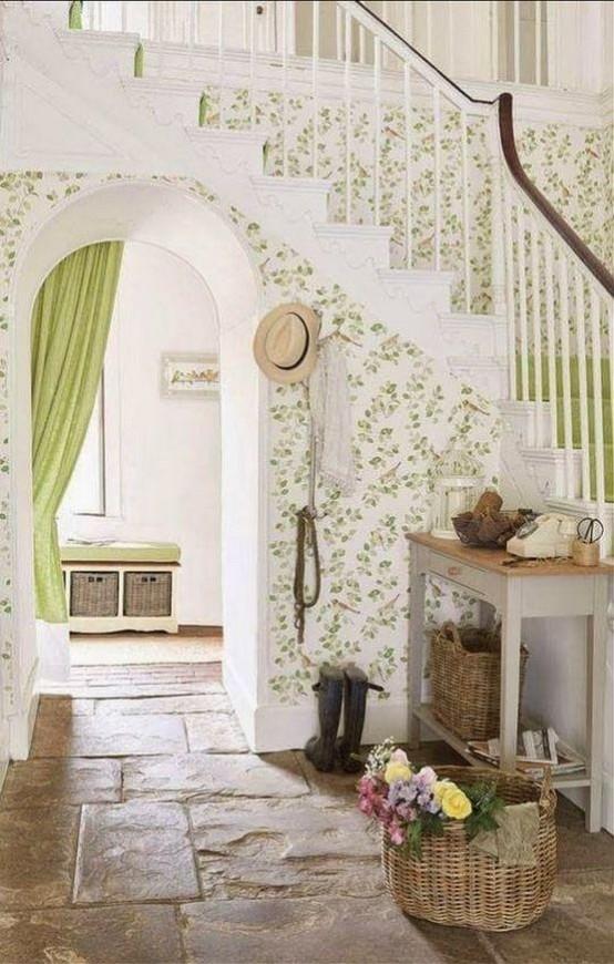 un grazioso ingresso neutro e verde con carta da parati stampata, una consolle, cestini e una panca con cestini