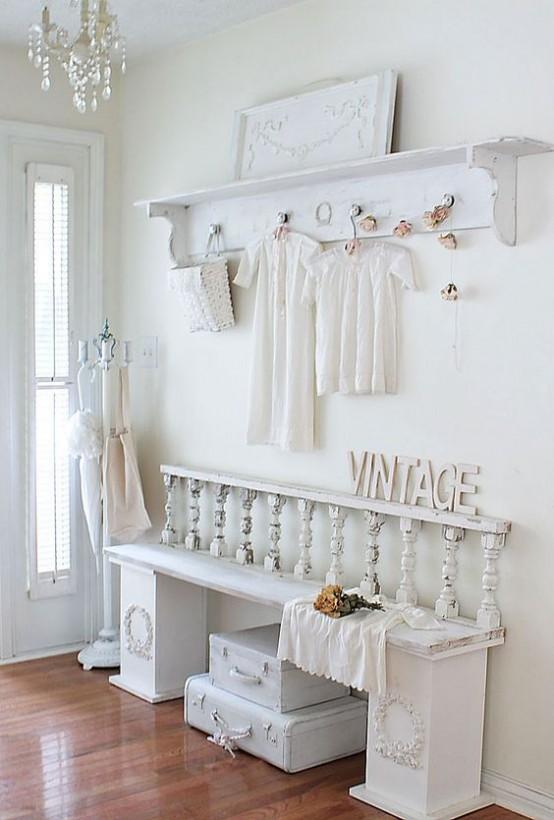 un ingresso shabby chic tutto bianco con un appendiabiti, una panchina, alcune valigie sotto la panchina e alcuni vestiti carini