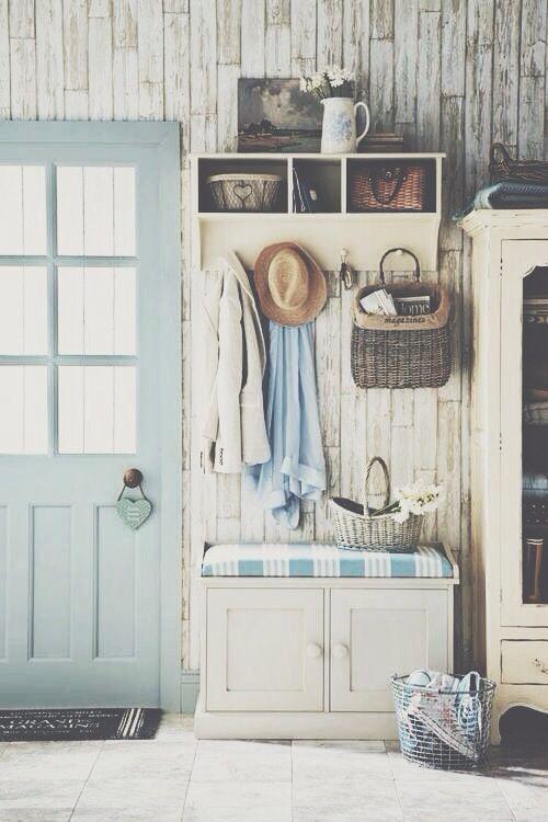 un bellissimo ingresso shabby chic con pareti in legno sbiancato, un mobile contenitore, un armadio e un sedile e una porta pastello