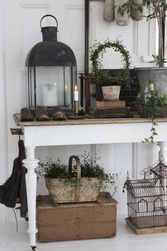 uno shabby chic incontra un ingresso rustico con una consolle, scatole, lanterne a candela, un cestino e vegetazione tutt'intorno