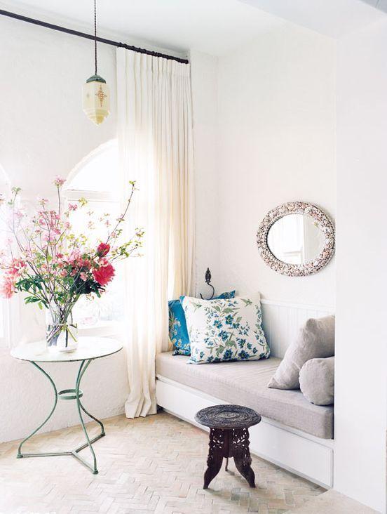 un ingresso neutro con tende, una lampada a sospensione, un comodo divano letto, uno specchio e uno sgabello più un elegante tavolino da caffè vintage
