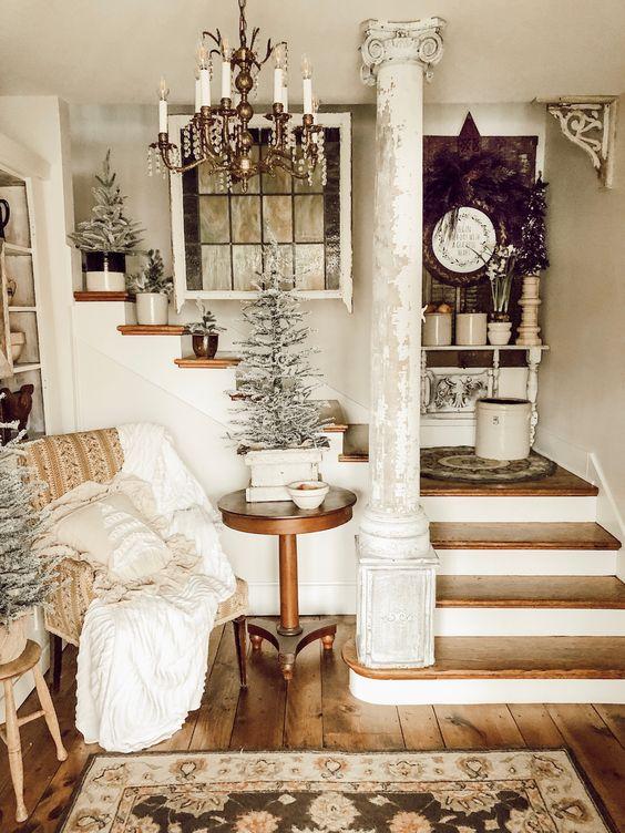 un'accogliente entrata shabby chic con una sedia imbottita, un tavolo di legno, alberi innevati in vaso e un tappeto