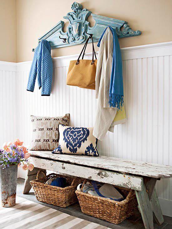 un luminoso ingresso shabby chic con battiscopa bianco, una panca in legno, cesti, cuscini e un appendiabiti blu