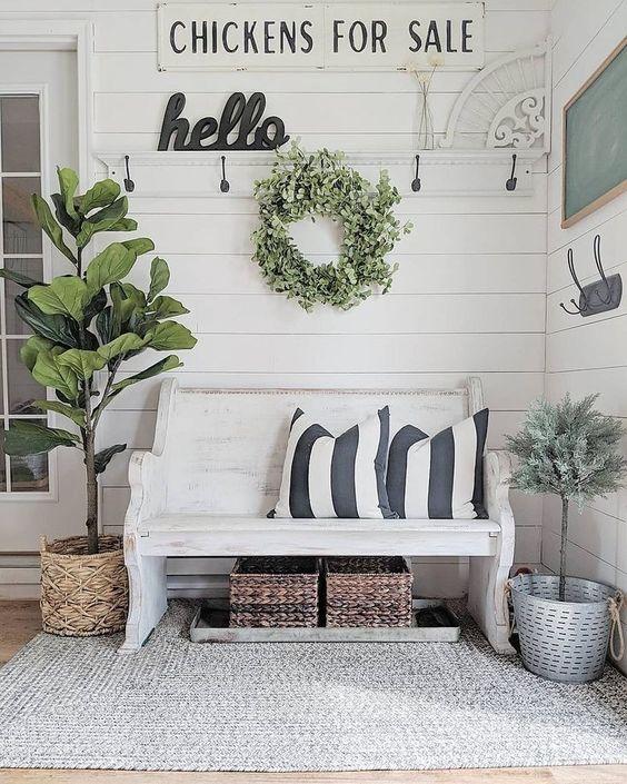 una fattoria incontra un ingresso shabby chic con cartelli, una panchina bianca, cesti e piante e alberi in vaso