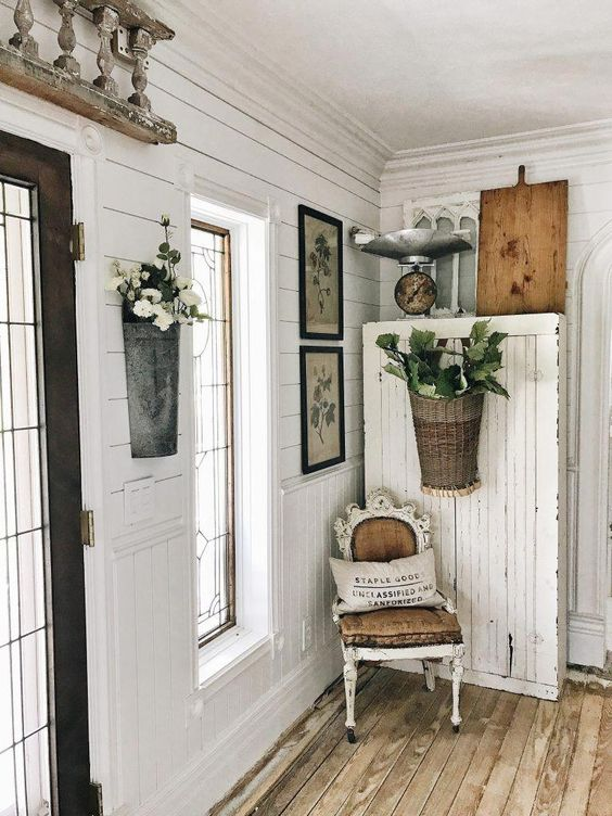 un ingresso shabby chic con un comò, piante in vaso e fiori, una sedia imbiancata a calce, opere d'arte