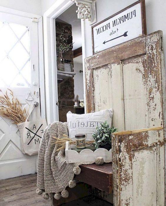 un ingresso shabby chic di una fattoria con segni, una panca in legno, grano, verde e una coperta in maglia