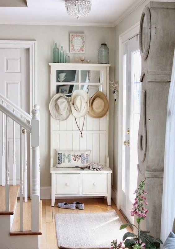 un ingresso shabby chic con un mobile contenitore con un sedile, un tappeto, bottiglie e un orologio da pavimento imbiancato
