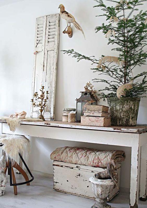 un ingresso shabby chic con una lunga consolle, una cassapanca sotto, uno sgabello, una persiana, candelabri e lanterne a candela