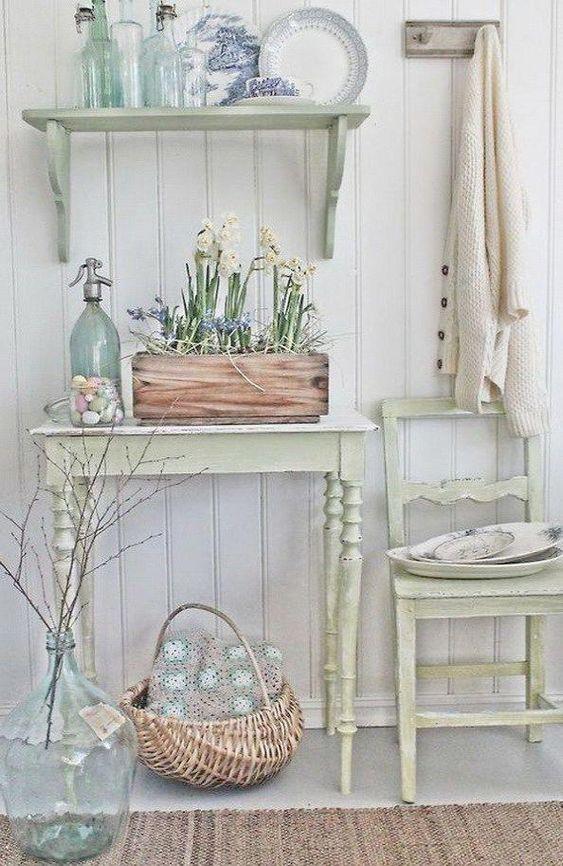 un ingresso shabby chic neutro con mobili pastello: una sedia, una console, uno scaffale, una scatola con fiori e un cestino
