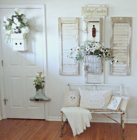 un'entrata shabby chic bianca con una panca in metallo, fiori in vaso e vegetazione, persiane alle pareti e insegne