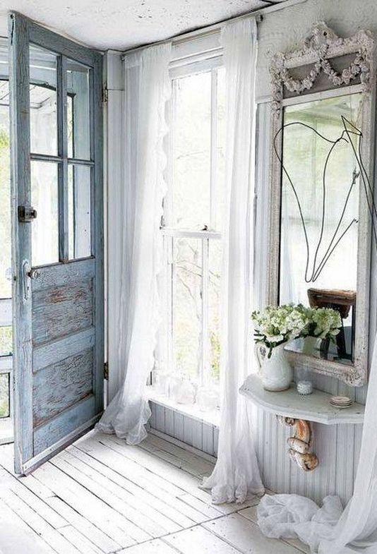un arioso ingresso shabby chic con una porta blu, un grande specchio, una mensola galleggiante, tende in tulle e alcune fioriture