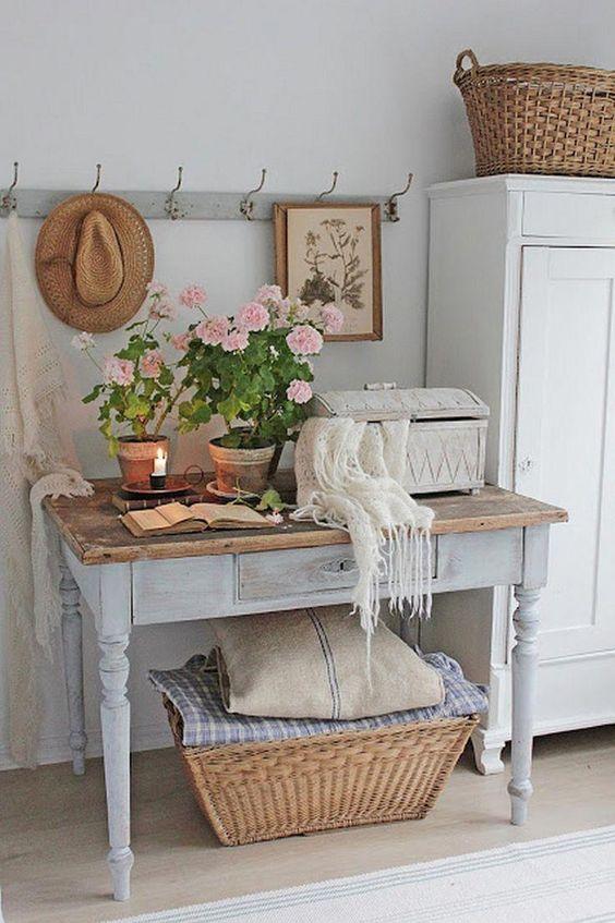 un ingresso shabby chic con un armadio, una consolle imbiancata con un piano in legno, un cestino, fiori in vaso e arte