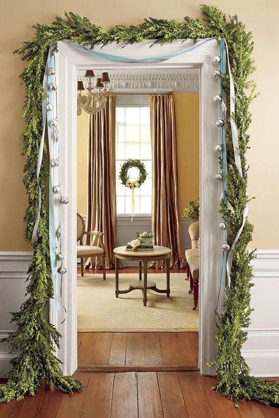 una ghirlanda verde che incornicia la porta e alcune grandi campane appese a nastri per un look chic e raffinato