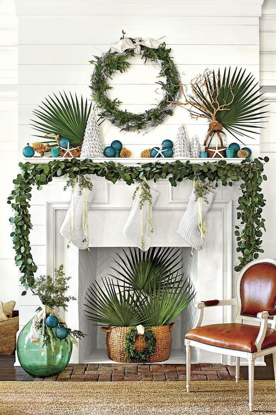 una ghirlanda verde sulla mensola del camino, una ghirlanda verde e foglie tropicali per lo stile natalizio in spiaggia
