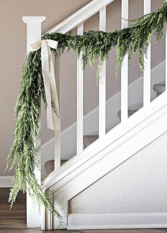 una ghirlanda verde con fiocchi bianchi per decorare la tua ringhiera in stile rustico con un tocco vintage