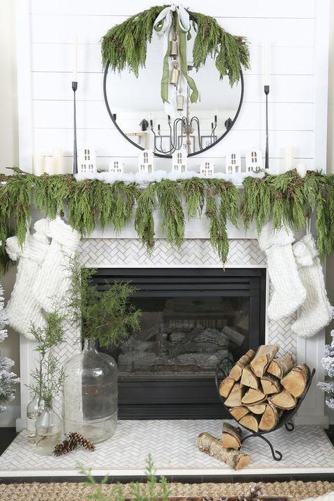 una lussureggiante ghirlanda sempreverde sulla mensola del camino, specchio e calze bianche che pendono dalla mensola del camino