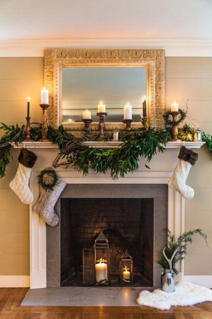 una ghirlanda di vegetazione lussureggiante e calze neutre che pendono più candele a colonna in candelabri in legno per uno stile elegante