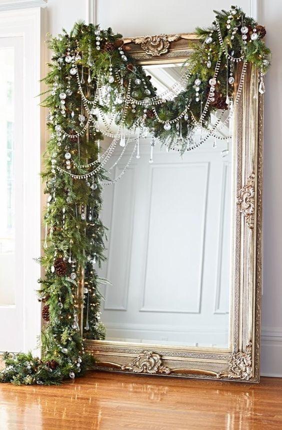 una lussureggiante ghirlanda sempreverde con pigne e cristalli più perline copre il grande specchio portando una forte atmosfera natalizia nello spazio