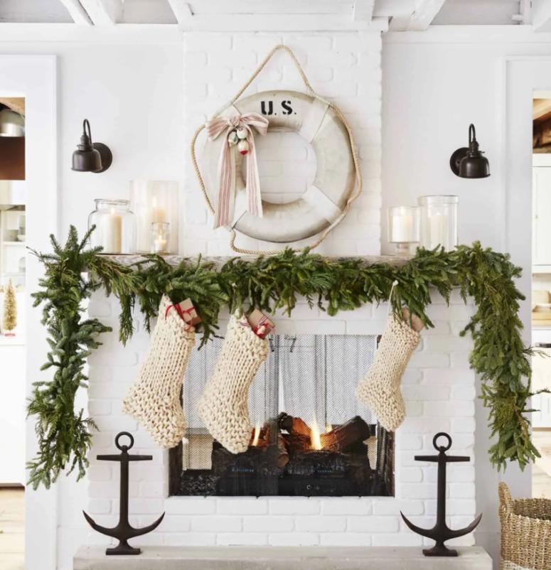 una lussureggiante ghirlanda sempreverde sulla mensola del camino, calze bianche lavorate a maglia per un grazioso spazio natalizio costiero