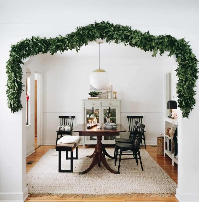 una ghirlanda di vegetazione lussureggiante che copre la porta per portare un'atmosfera natalizia leggera e chic nello spazio