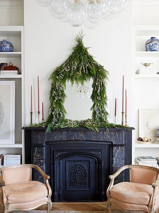 una ghirlanda di vegetazione lussureggiante con mini ornamenti che coprono uno specchio sulla mensola del camino aggiunge un bizzarro tocco holidya allo spazio