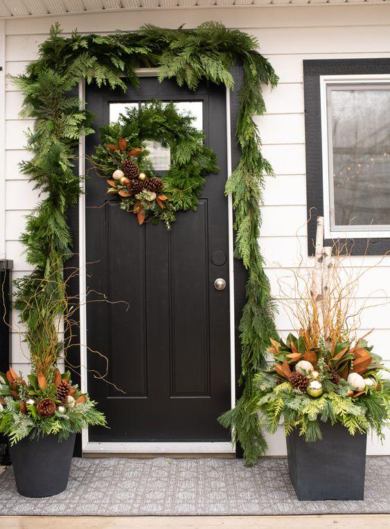 una ghirlanda verde che copre la porta, una ghirlanda coordinata e composizioni in vasi con ornamenti e pigne