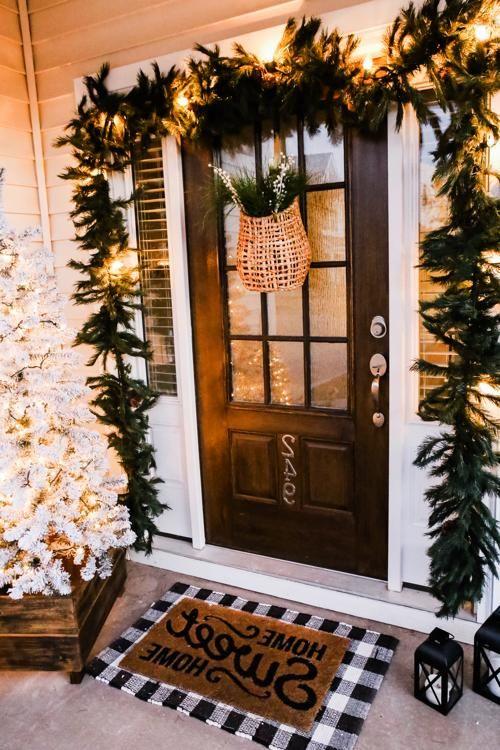 una lussureggiante ghirlanda sempreverde con luci sopra la porta, un albero di Natale floccato in una cassa e un cesto con vegetazione