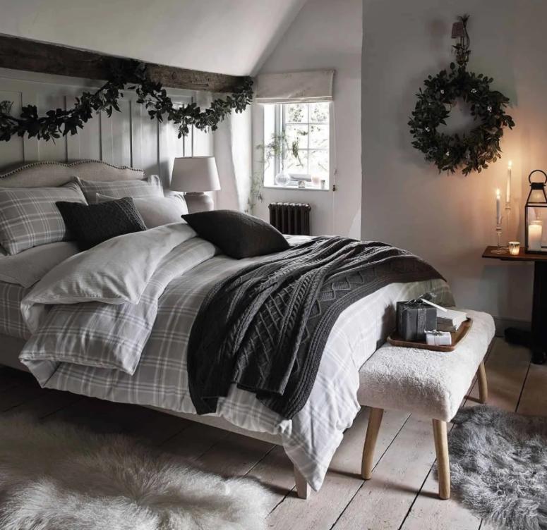 una semplice ghirlanda verde sopra il letto e una ghirlanda abbinata sul muro conferiscono un leggero tocco natalizio allo spazio