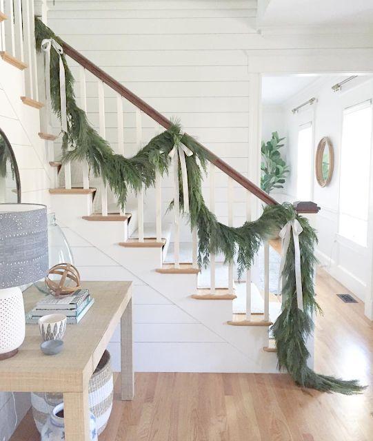 una ghirlanda sempreverde con fiocchi di seta neutri per decorare la ringhiera è un'idea elegante e bella