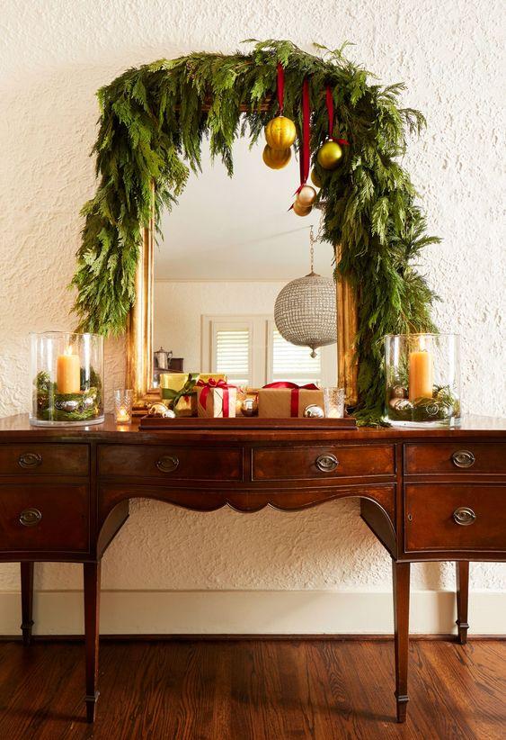 un buffet vintage ricoperto da una ghirlanda di vegetazione lussureggiante, con ornamenti d'oro su nastri rossi e scatole regalo sembra molto chic