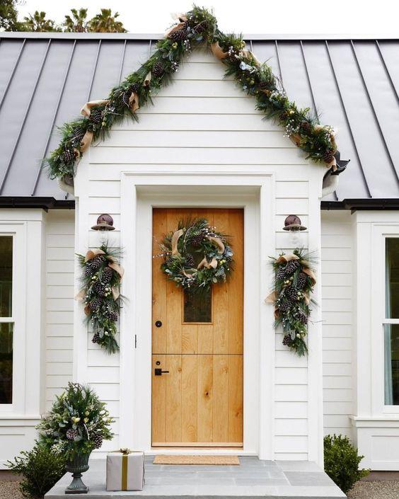 una ghirlanda sempreverde con pigne e nastri di juta che coprono il portico e mazzolini e ghirlande che si abbinano