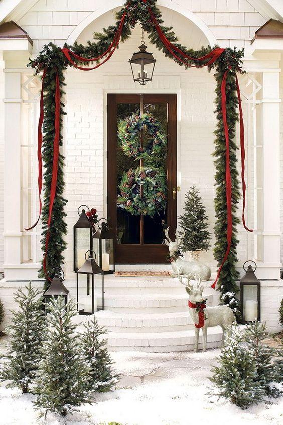 una ghirlanda sempreverde sopra il portico con nastri e fiocchi, ghirlande sempreverdi con pigne e alberi di Natale innevati