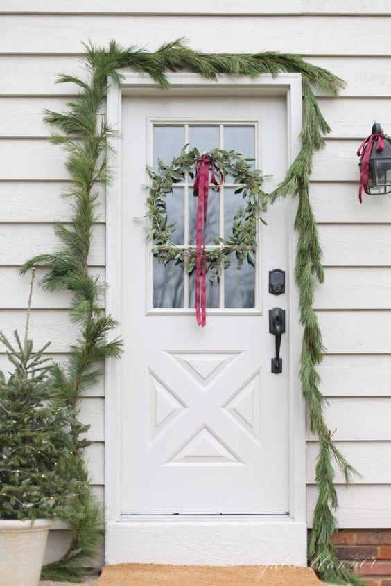 una semplice ghirlanda sempreverde che copre la porta, mini alberi di Natale in vaso e una ghirlanda verde con un fiocco di nastro rosso
