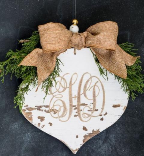 un ornamento natalizio in compensato bianco con sempreverdi, un fiocco di juta e monogrammi più perline è una bella idea vintage
