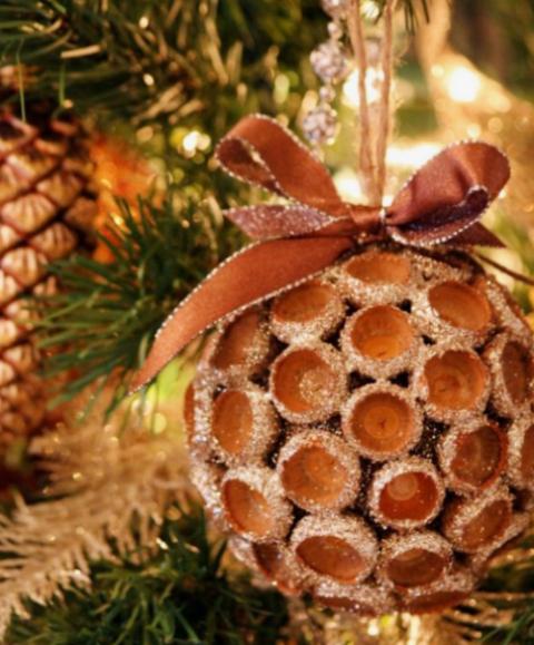 un ornamento natalizio con ghiande glitterate con un fiocco abbinato è un'idea divertente e molto naturale di una decorazione invernale