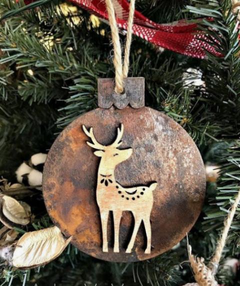 un ornamento natalizio in legno con decorazioni ruggine e un piccolo cervo in legno è super carino e carino